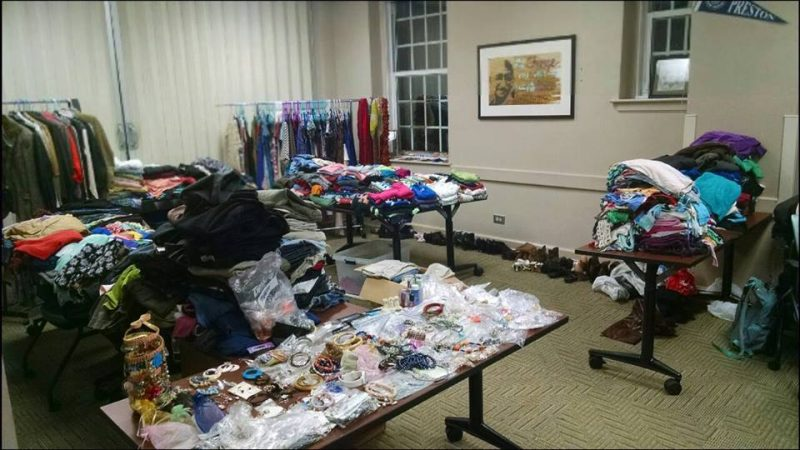a photo of the clothes collected for the clothes drive. There are five tables of clothes, plus two clothes racks, plus a table of jewelry.